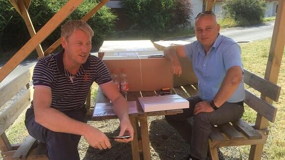 Zwei Männer sitzen auf einer Bank an einem Tisch.