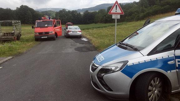Ein Polizei- und ein Feuerwehrauto stehen an einer Straße.
