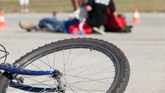 Fahrrad liegt am Boden, im Hintergrund wird ein Verletzter versorgt