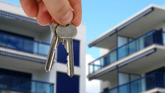 Wohnungsschlüssel, im Hintergrund moderne Wohnhäuser.