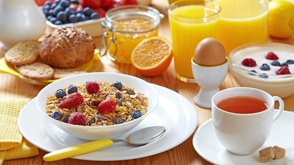 Ein Frühstückstisch mit Müsli, Tee, Brötchen, einem Ei und Quark