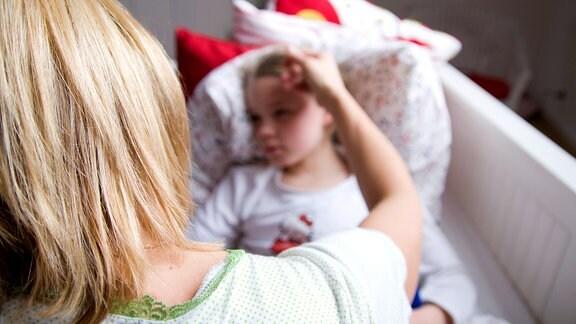 Mädchen liegt im Bett und wird von Mutter gestreichelt.