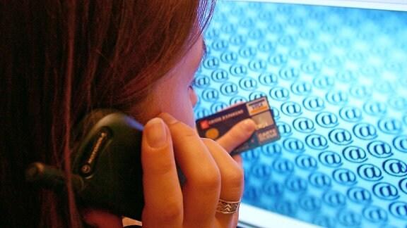 Telefonierende Frau mit Kreditkarte in der Hand