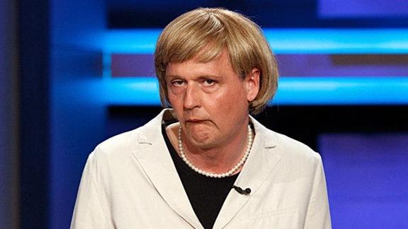 Hängende Mundwinkel und Perlenkette - Wer kann das wohl sein? Reiner Kröhnert als Angela Merkel.