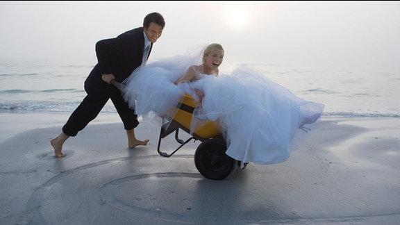 Hochzeit - Bräuigam schiebt Braut in einer Schubkarre