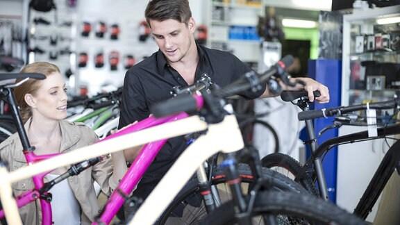 Eine junge Frau läßt sich beim Fahrradkauf von einem jungen Verkäufer beraten.