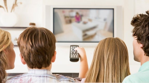 Vier junge Menschen schauen Fernsehen