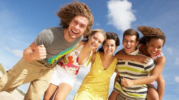 Fünf junge Leute umarmen sich und lachen.