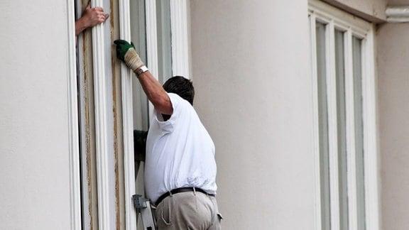 ein Bauarbeiter wechselt an einem Haus die Fenster aus