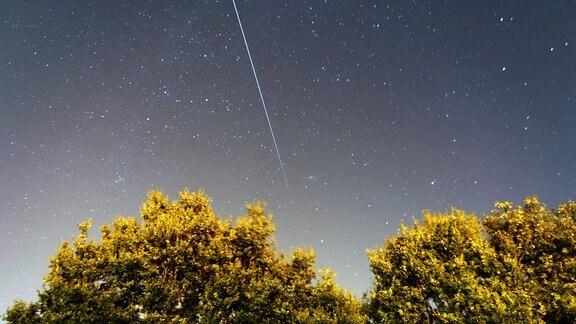 Die Internationale Raumstation (ISS) hinterlässt in dieser 61-Sekunden-Belichtung eine Spur während sie den Nachthimmel durchfliegt.