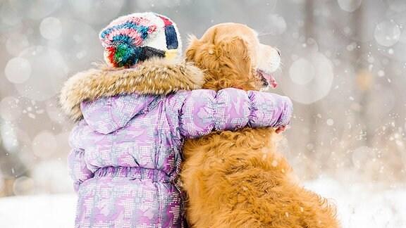 Ein kleines Mädchen und ein Hund sitzen im Schnee