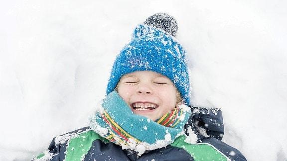 Ein Kind liegt im Schnee.
