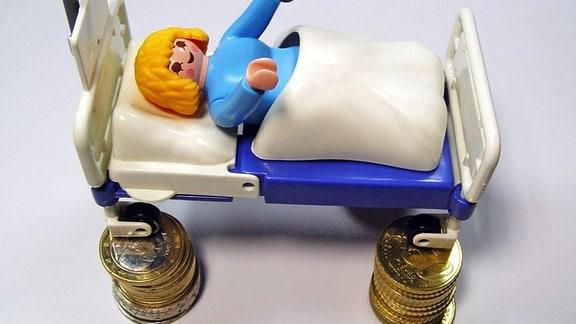 Spielzeug-Krankenhausbett steht auf Geldmünzen