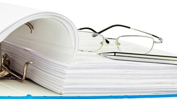 Auf einem aufgeschlagenem Dokumentenordner ist ein Stift und eine Brille abgelegt.