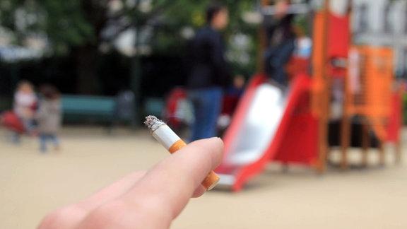 Symbolbild zum Rauchverbot auf Spielplätzen - im Vordergrund eine brennende Zigarette im Hintergrund ein Spielplatz.