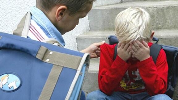 Ein Schulkind tröstet einen Mitschüler (Symbolbild).