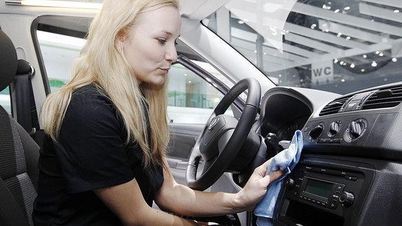 Eine Frau säubert den Innenraum eines Autos.