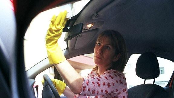Frau putzt den Autoinnenraum.