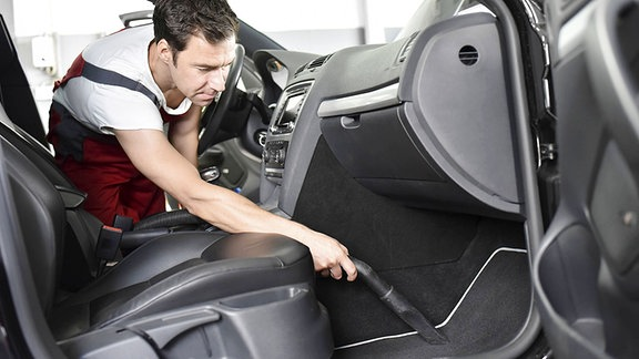 Mann saugt den Autoinnenraum.