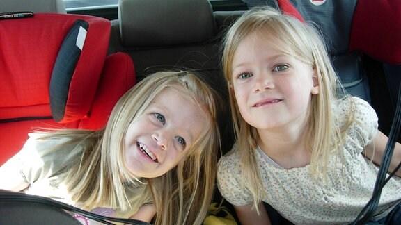 Zwei kleine Mädchen auf ihren Autokindersitzen.