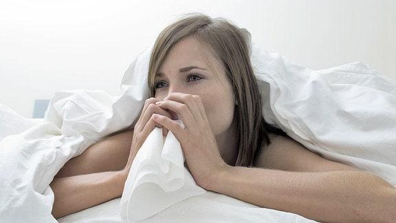Eine junge Frau liegt erkältet im Bett.