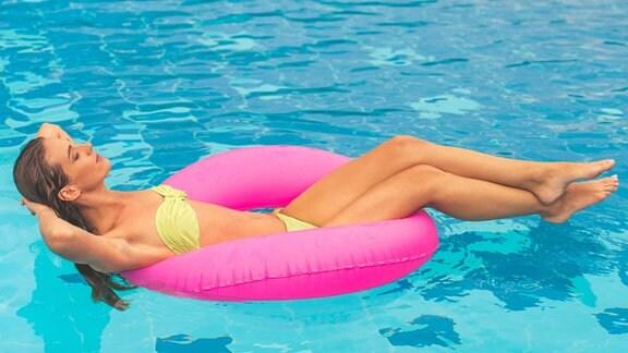 Eine Frau nimmt ein Sonnenbad auf einer Liege an einem Pool.