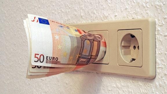 Geldscheine stecken in einer Steckdose