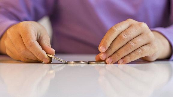 Die Hände eines Kindes zählen Geldmünzen auf einem Tisch