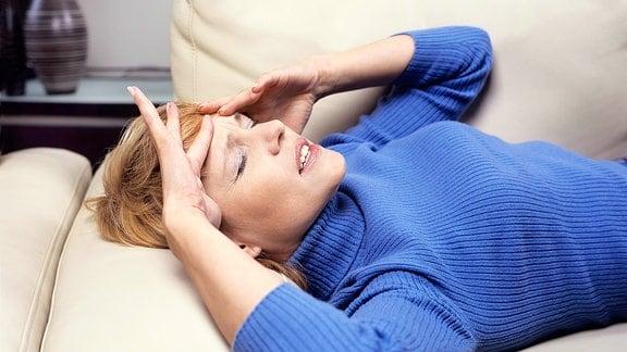 Eine Frau liegt mit Kopfschmerzen auf einer Couch