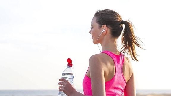 Eine junge blonde Frau in Sportkleidung und mit Kopfhörern steht mit einer Getränkeflasche in der Hand an einem Strand