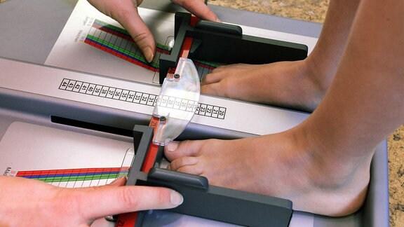 Nackte Kinderfüße werden mit einem Fußmessgerät vermessen