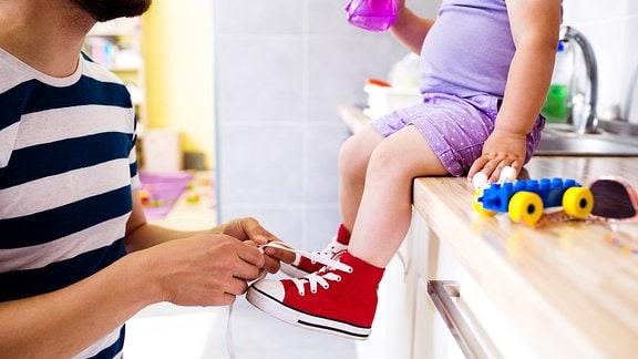 Ein Vater zieht seiner kleinen Tochter Schuhe an.