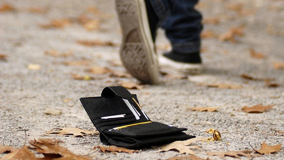Jemand geht über einen mit Herbstlaub bedeckten Weg. Hinter ihm liegt auf dem Weg eine verlorene Brieftasche.