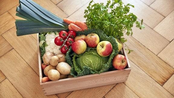 Auf einem Parkettfußboden steht eine Holzkiste mit Obst und Gemüse