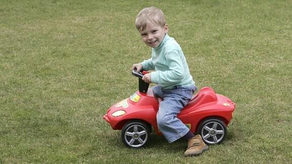 Ein Junge auf einem Bobbycar