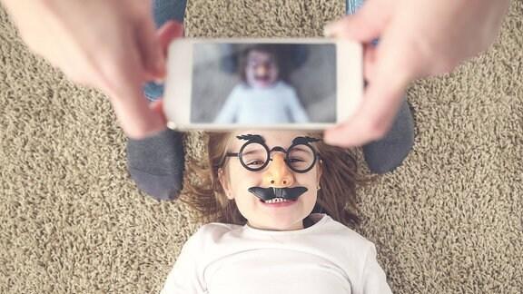 Eine Mutter fotografiert ihre liegende, mit falschen Augenbrauen und Schnurrbart verkleidete Tochter.