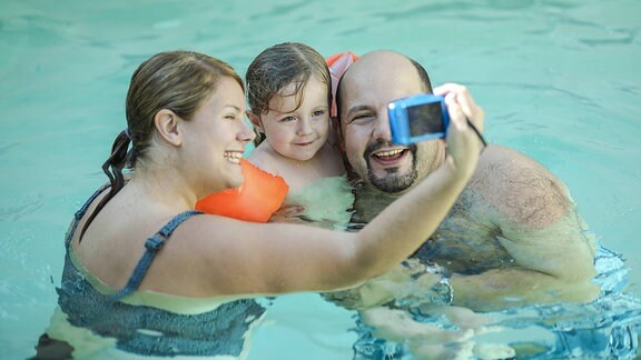 Eine Familie macht ein Selfie im Schwimmbad