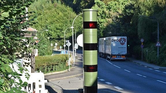 Eine moderne Blitzersäule steht an einer Straße.