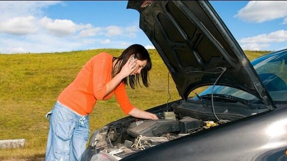 Eine Frau beugt sich über den geöffneten Motorraum ihres liegengebliebenen Autos.