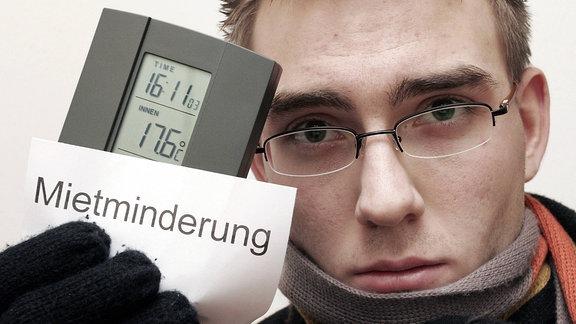 """Ein junger, warm angezogener Mann, hält in seiner Hand ein Thermometer, das eine Innentemperatur von 17,6 Grad anzeigt, sowie einen Zettel mit der Aufschrift """"Mietminderung"""""""
