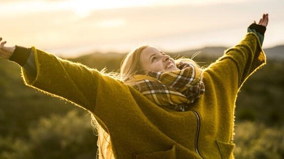 Eine junge Frau streckt draußen lachend ihre Arme aus.