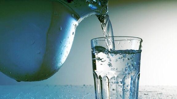 Aus einer Karaffe wird Wasser in ein Glas gegossen.