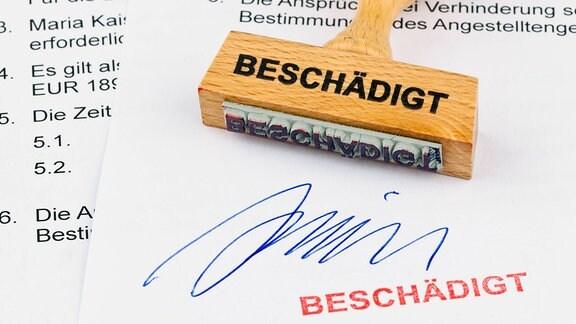 """Ein Stempel, Aufschrift """"Beschädigt"""", aus Holz liegt auf einem Dokument."""