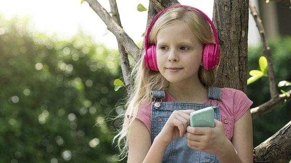 Ein Mädchen mit Kopfhörern spielt an ihrem Handy
