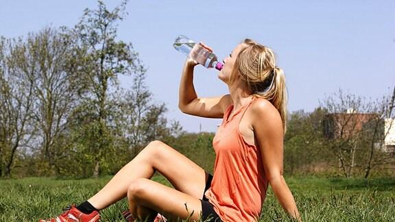 Eine Joggerin trinkt während einer Pause Wasser aus einer Flasche.