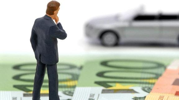 ein Spielzeugauto mit Fahrer stehen auf Geldscheinen