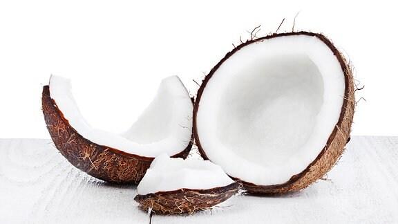 Teile einer aufgeschlagenen Kokosnuss vor einer Strandkulisse.