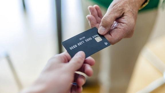 Zwei Hände halten Kreditkarten-Modell