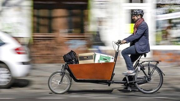 Ein Mann fährt mit einem Lastenrad