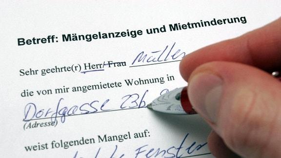 """Eine Hand füllt mit einem Kugelschreiber einen Musterbrief mit dem Betreff """"Mängelanzeige und Mietminderung"""" aus."""